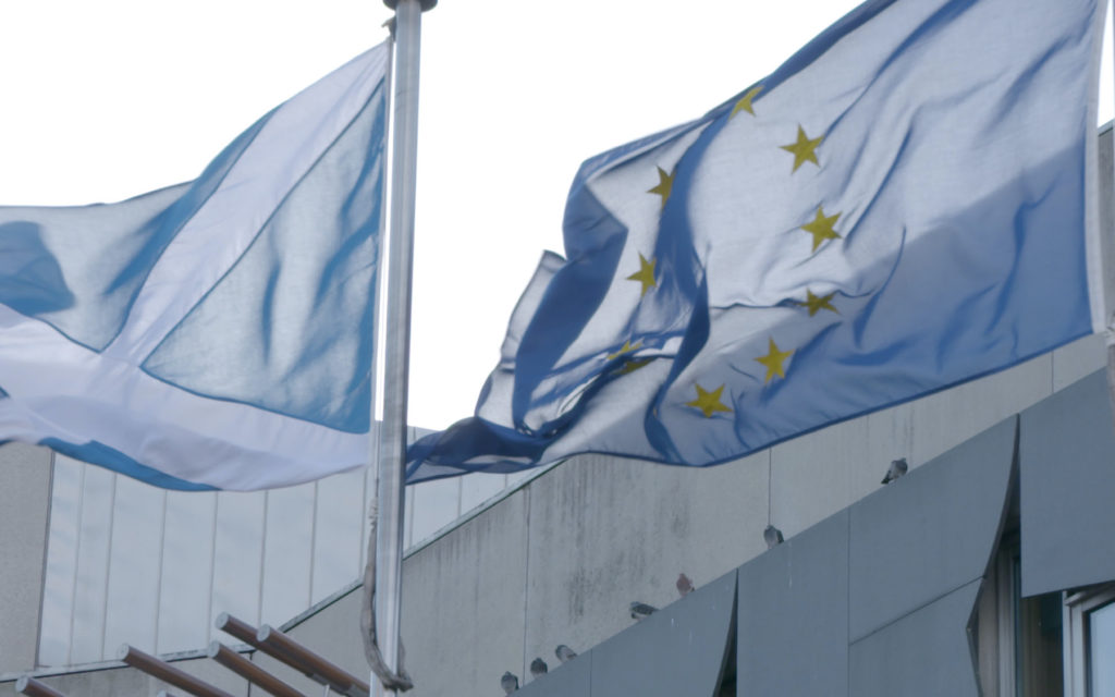 The Scottish flag and EU flag blowing in the wind outside of the Scottish Parliament building