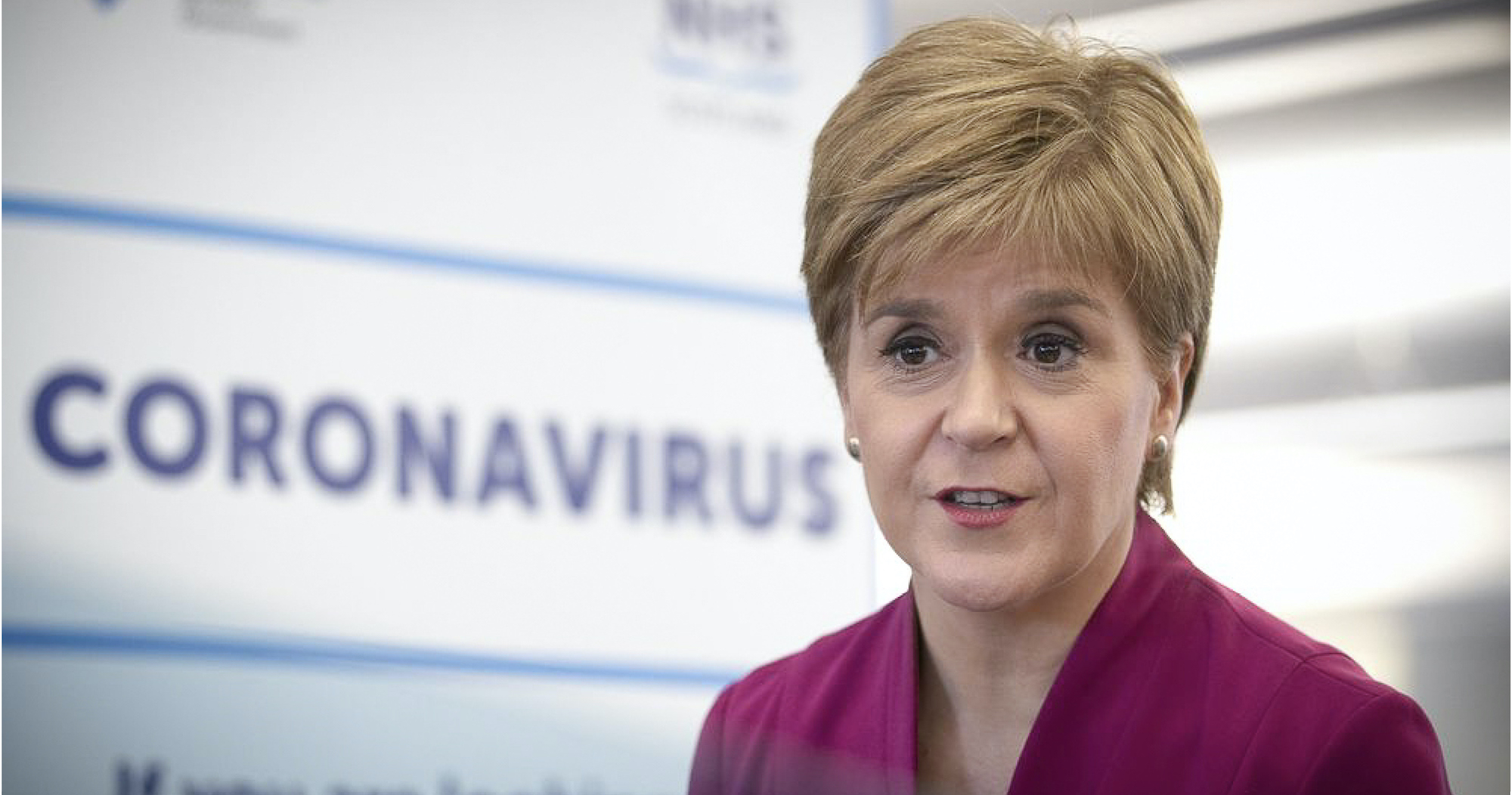 First Minister of Scotland Nicola Sturgeon in front of a NHS Scotland Coronavirus sign
