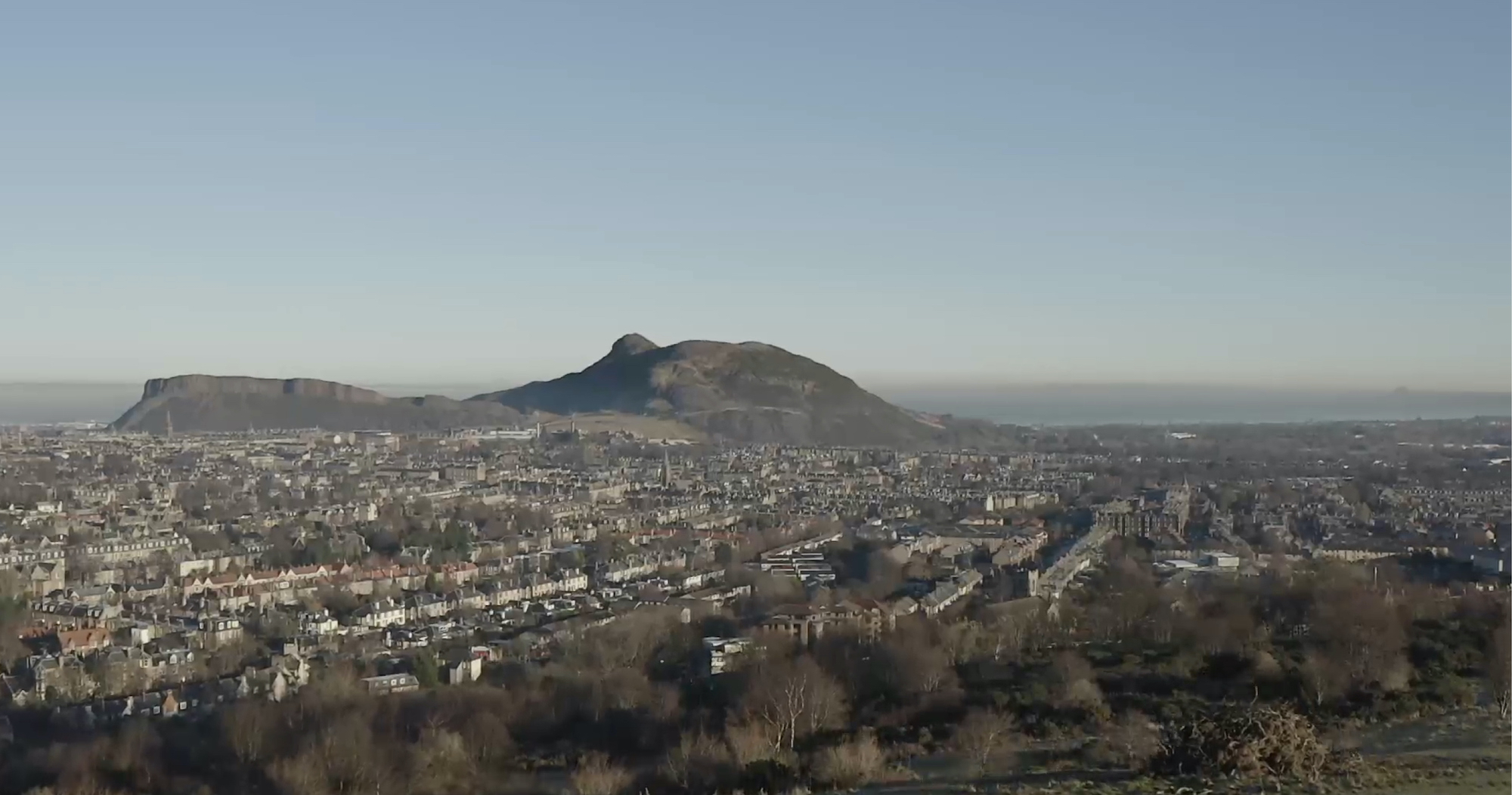 A view of Edinburgh, Scotland, with the Salisbury Crags in the background on a sunny day