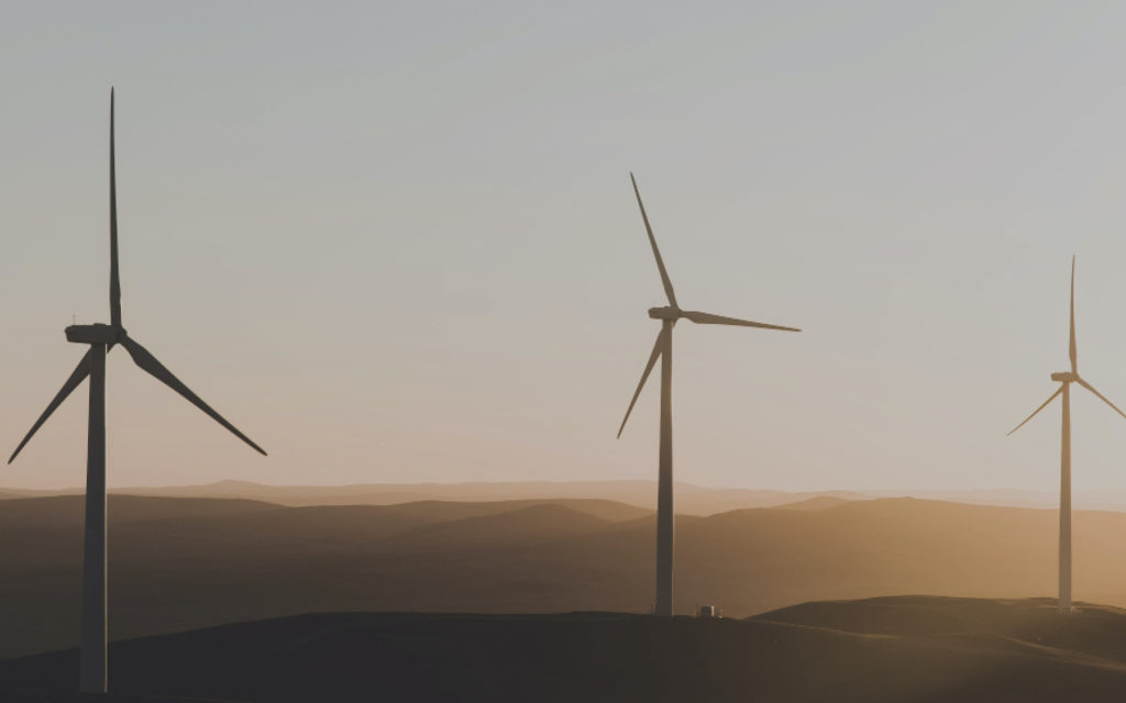 Three wind turbines in a hilly landscape
