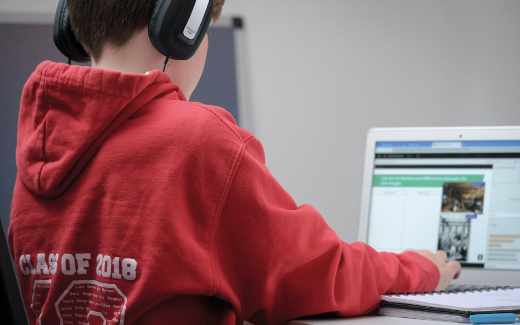 A young boy in a red hoodie and headphones, using a laptop