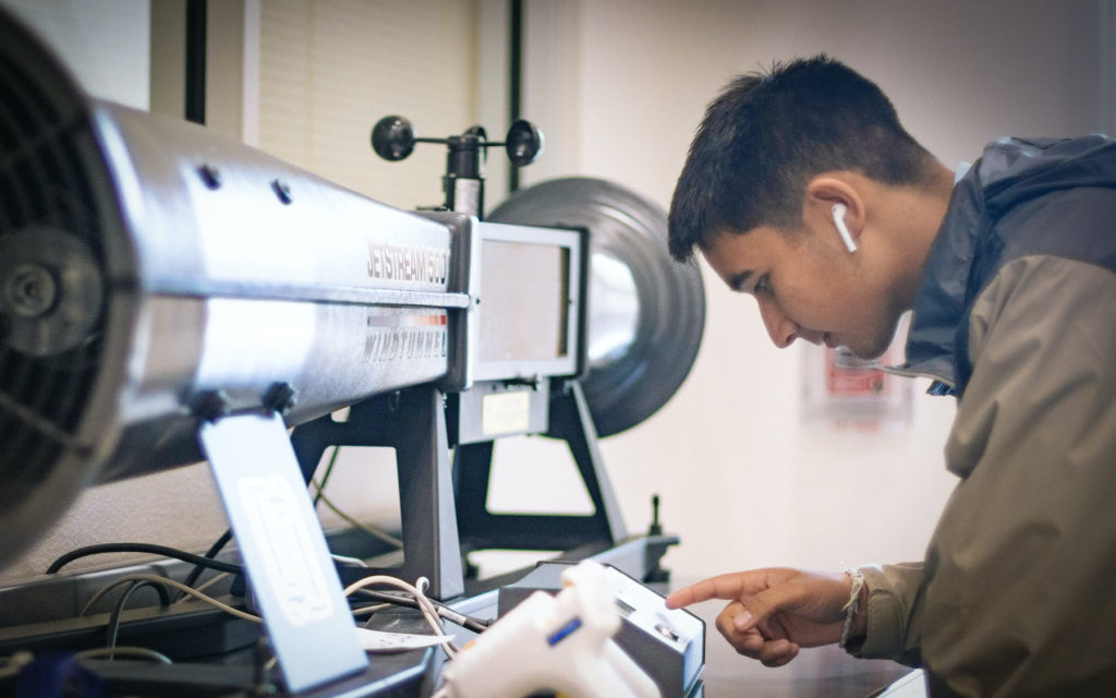 A young man working on a piece of machinery