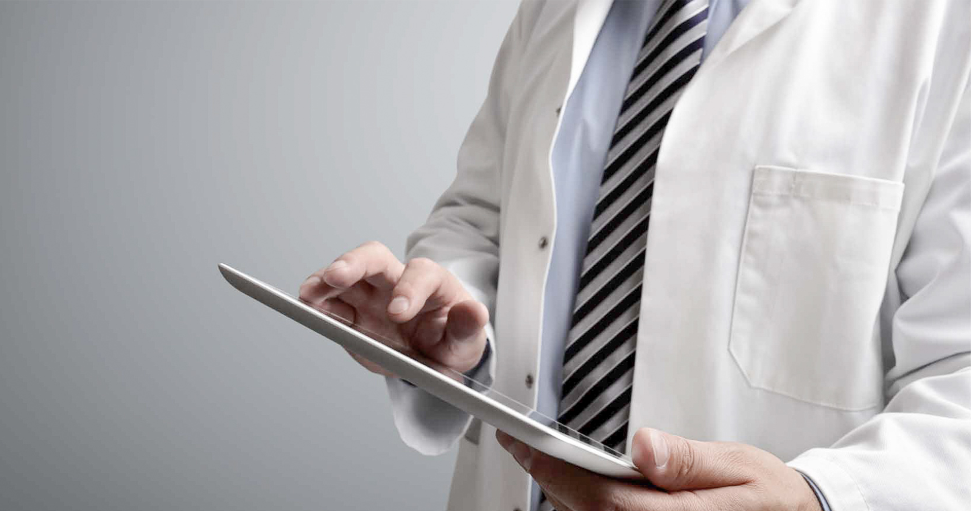 A close up of a person in a white medical coat holding a tablet device
