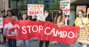 """Protestors against the proposed Cambo oil field in Scotland holding signs and a red banner reading """"Stop Cambo"""""""